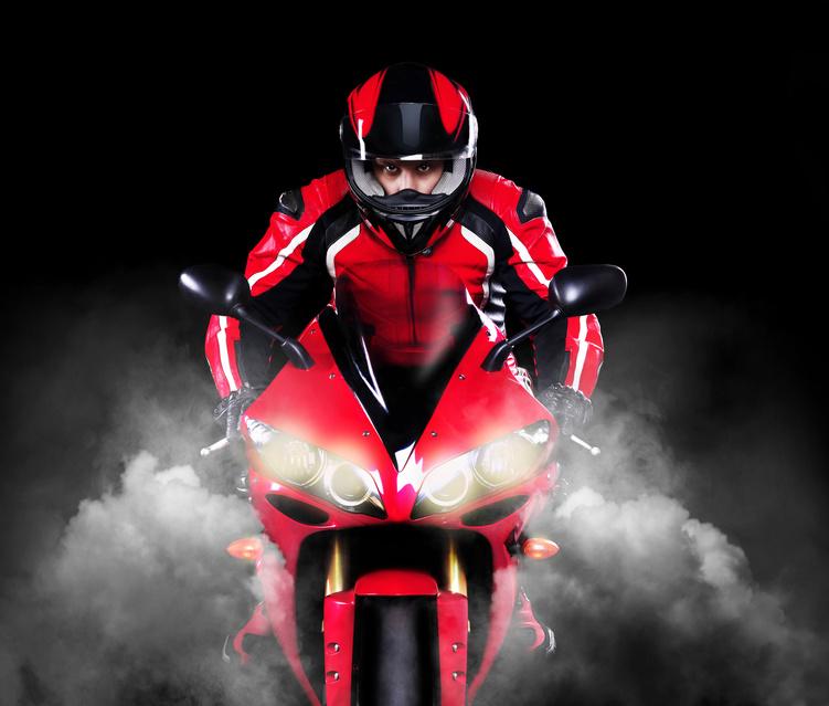 Motorcyclist riding motorbikeover black background
